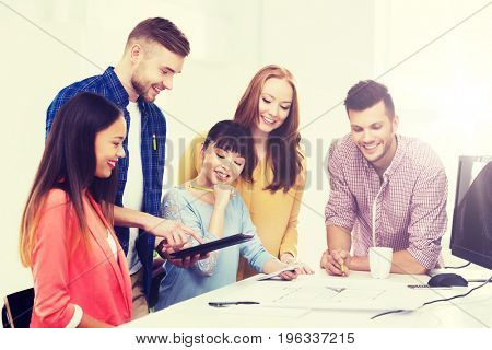 business, startup, education and people concept - happy creative architect team or students with blueprint working at office
