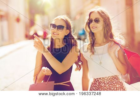 sale, consumerism and people concept - happy young women with shopping bags pointing finger in city