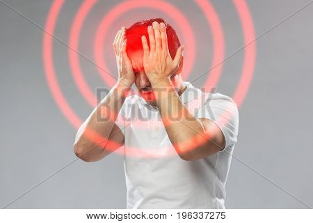 people, pain and stress concept - unhappy man suffering from head ache touching his forehead and eyes over gray background