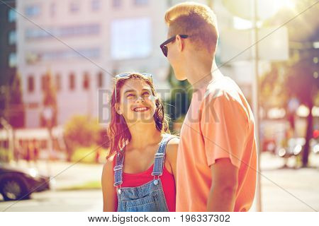 holidays, vacation, love and people concept - happy smiling teenage couple hugging and looking at each other at summer city