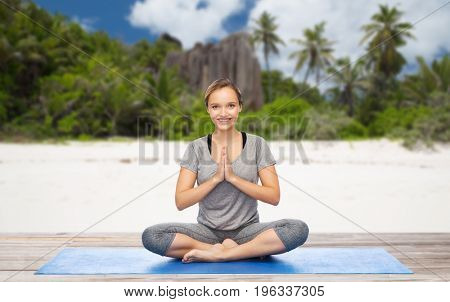 fitness, people and healthy lifestyle concept - happy smiling woman doing yoga meditation in lotus pose on mat over exotic tropical beach background