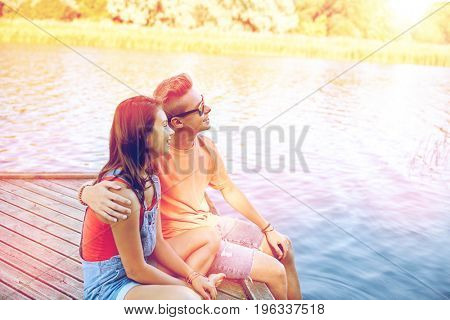 holidays, vacation, love and people concept - happy teenage couple hugging on river berth at summer