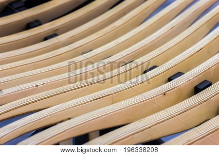 Beige textured wooden background. Abstract pattern from diagonal lines of wooden bench or armchair, selective focus. With place for your text, for background use