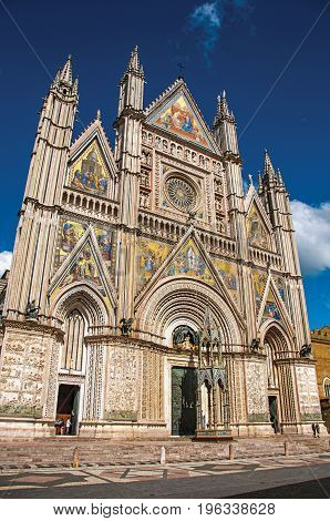Facade view of the opulent and monumental Orvieto Cathedral (Duomo) under sunny blue sky in Orvieto, a pleasant and well preserved medieval town. Located in Umbria, central Italy