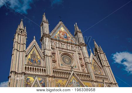 Facade details of the opulent and monumental Orvieto Cathedral (Duomo) under sunny blue sky in Orvieto, a pleasant and well preserved medieval town. Located in Umbria, central Italy