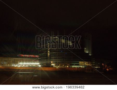 STRASBOURG FRANCE - NOV 30 2017: European Parliament in Strasbourg at night with traces from star filter and all European Union Flags waving