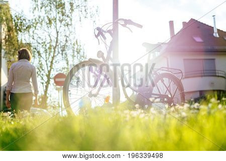 Woman walking near Beautiful modern city urban bicycle parked on calm street town with majestic sun flare sunlight behind - sport concept staying fit concept going to work by bike at sunset or sunrise