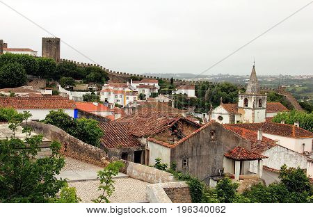 Obidos, Portugal. Beautiful tiny cobblestoned streets, walls, and roofs on different levels. Obidos is an ancient medieval Portuguese village originated in the 11th century and still situated within the same castle walls.