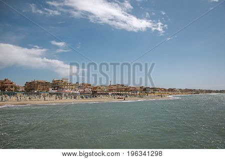 Overview of the beach and town of Ostia between the Mediterranean sea and sunny sky. The town is a seaside resort and ancient port of Rome. Located in the Lazio region