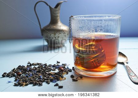 Closeup Glass Of Hot Tea With Tea Strainer And Tea Leaves