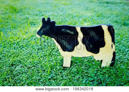 Wooden painted black and white dairy cow on green grass