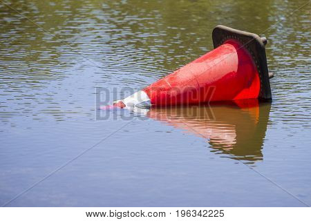 Red traffic cone floating in water on flooded street danger weather and communication concepts