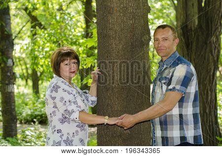 A married couple posing on nature near a tree.