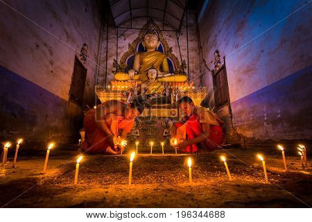 Novice Monk fire candles to the Buddha in thailand