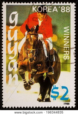 Moscow Russia - July 21 2017: A stamp printed in Guyana shows the galloping horseman devoted to the Olympic Games in Korea circa 1988