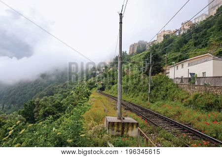 View of woods and houses around train tracks on cloudy and foggy day. Near the Lake of Albano, a quiet and bucolic countryside region near Rome. Located in the Lazio region, central Italy