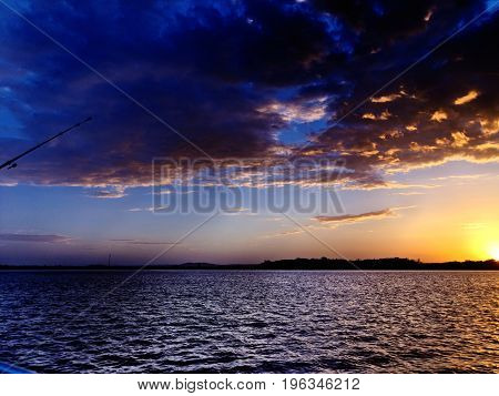 Vivid orange and yellow cloudy ocean sunset with dark backlit clouds and water reflections. Photograph was taken off the Australian East Coast