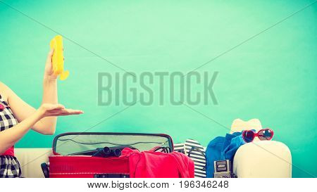 Young Woman Packing Suitcase On Couch