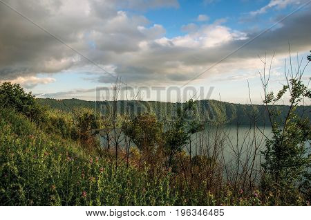 View of the slopes, forests and hills of Lake Albano in a cloudy sunset. Albano is a quiet and bucolic countryside region near Rome. Located in the Lazio region, central Italy