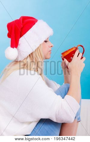Relaxation during Christmas time concept. Woman in Santa hat holding holiday mug and drinking hot drink coffee or tea enjoying her leisure time for relax.