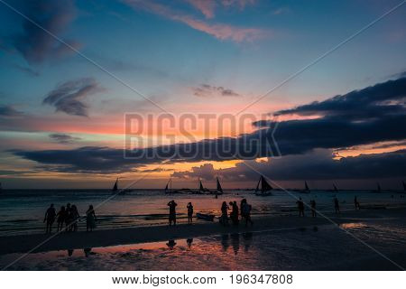 Silhouette of many people looking the amazing sunset of Boracay from the White Beach Philippines. Clouds and boats compose the scene of this tropical island.