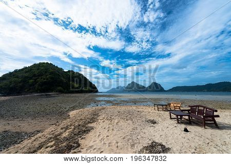 Wide angle view of rocks and the sea of El Nido Philippines. Tropical weather in this beautiful island. Chairs and tables beachfront