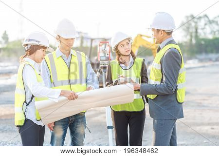 Businessman engineer and builder review blueprint during team meeting at construction site in the morning with sunlight