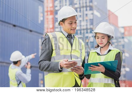 Secretary and businessman in logistic export import industry with shipping cargo container freight in background