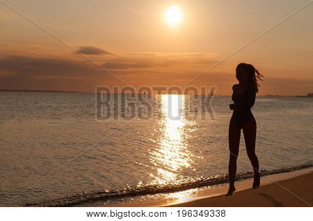 Silhouette Of A Young Woman Running On The Seaside At Sunset