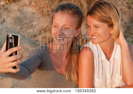 Two Beautiful Women Friends Taking Photos With A Smart Phone On The Beach At The Sunset
