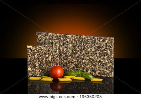 Two contemporary looking stone samples for kitchen and bathroom countertops on black glossy surface with pasta and tomato