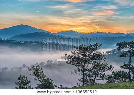 Sunrise in the mist with the mountain background.