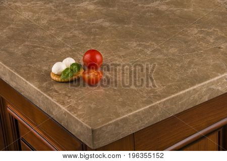 Modern brownish granite countertop with mozzarella and tomatoes on it