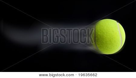 Tennis ball fast moving on black background leaving trail behind