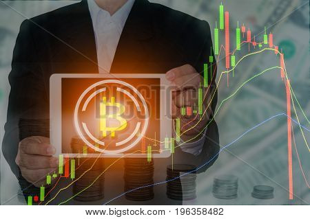 Bitcoin and Blockchain concept : Rise and fall of bitcoin price. Businessman holding tablet showing bitcoin symbol with price chart and money in background.