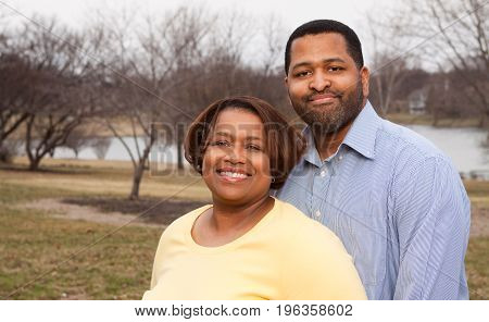 Loving African American couple hugging and smiling outside.