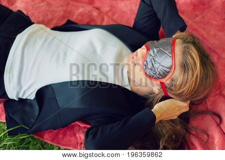 Young stylish Caucasian business lady in formal trendy suit is going to sleep or having nap on the red blanket in the public park wearing up eye mask. People lifestyle and leisure concept.