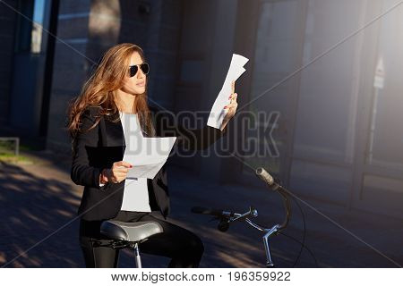 Business and achievement.Serious concentrated European corporate female worker in formal wear reading financial report during the break outdoors. Urban lifestyle ecology and transportation concept.