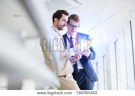 Businessmen using digital tablet in convention center