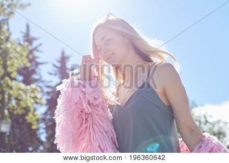People travel holidays and leisure concept.Rear view of young woman with long loose hair walking in adventure park at sunlight wearing eyeglasses and coatenjoying happy pleasant moment of vacations.