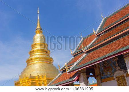 Thai Golden Pagoda And Chapel Roof Wat Phrathat Hariphunchai Woramaha Vihan, Lamphun, Thailand.