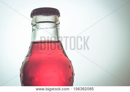 closeup soft drink red color in glass bottle.