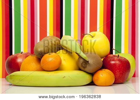 A bunch of fruits. Red and green apple, pear, orange, grapefruit, mandarin, kiwi, banana. On a reflective surface. Multicolored background with vertical stripes.