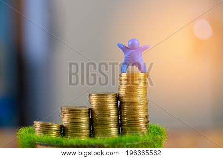 Miniature Human Figure Made From Blue Plasticine With Coins On Wooden Table. Shallow Focus, Soft Ton