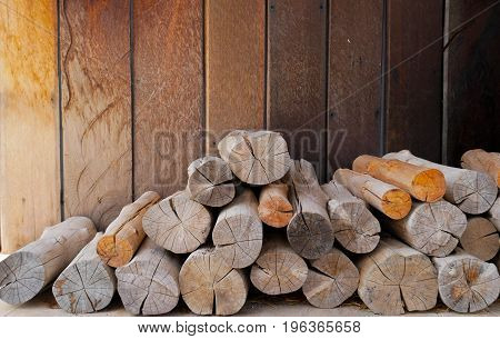 Pile of firewood and brown wooden wall. Preparation of firewood for the winter. Background space for text or image.