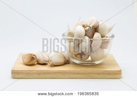 Fresh rood garlic on wooden board on glass cup on white background