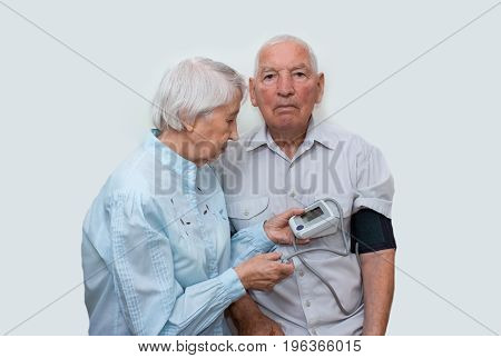 Apparatus measuring the pressure in the hands of an elderly woman and old man. Tonometer in the wrinkled hands of an elderly person. Concept of good health