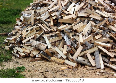 bunch of birch logs on the grass chopped by an axe. firewood for heating furnaces. stack.