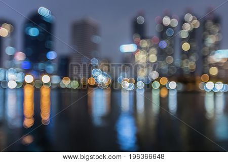 Reflection blurred bokeh light of city office building light night view abstract background