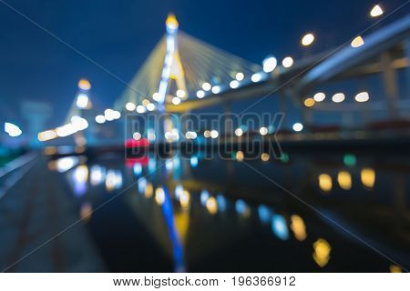Twilight blurred bokeh light suspension bridge with reflection abstract background